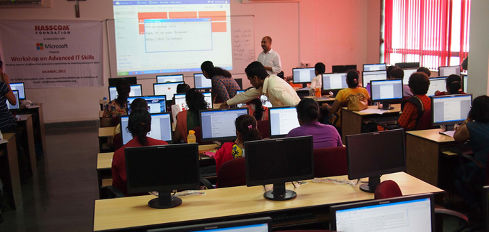 A photograph of a classroom setting arrangement where NGO professionals are getting trained in IT skills
