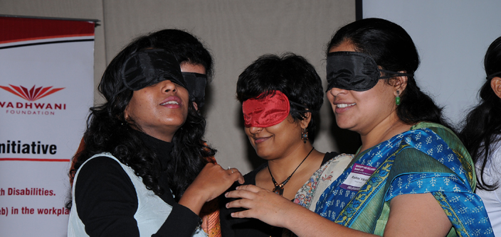 A photograph of a workshop where corporate representatives have been blindfolded to sensitize them on the issue of accessibility at workplace