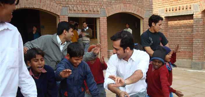 A photograph of corporate volunteers engaged in a fun activity with kids from underserved communities